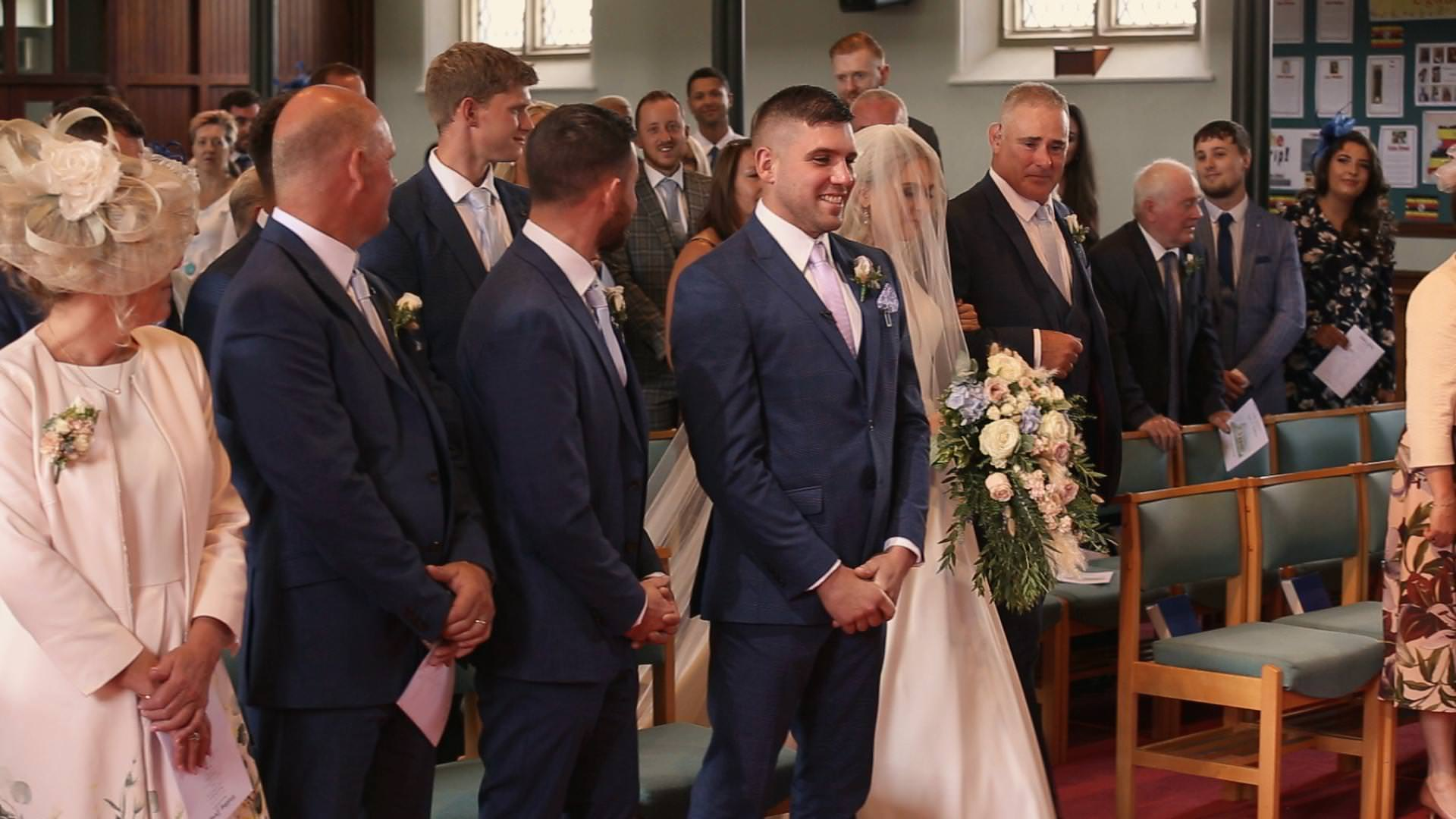 a groom looks happy as his bride walks down the aisle at St Johns in Burscough