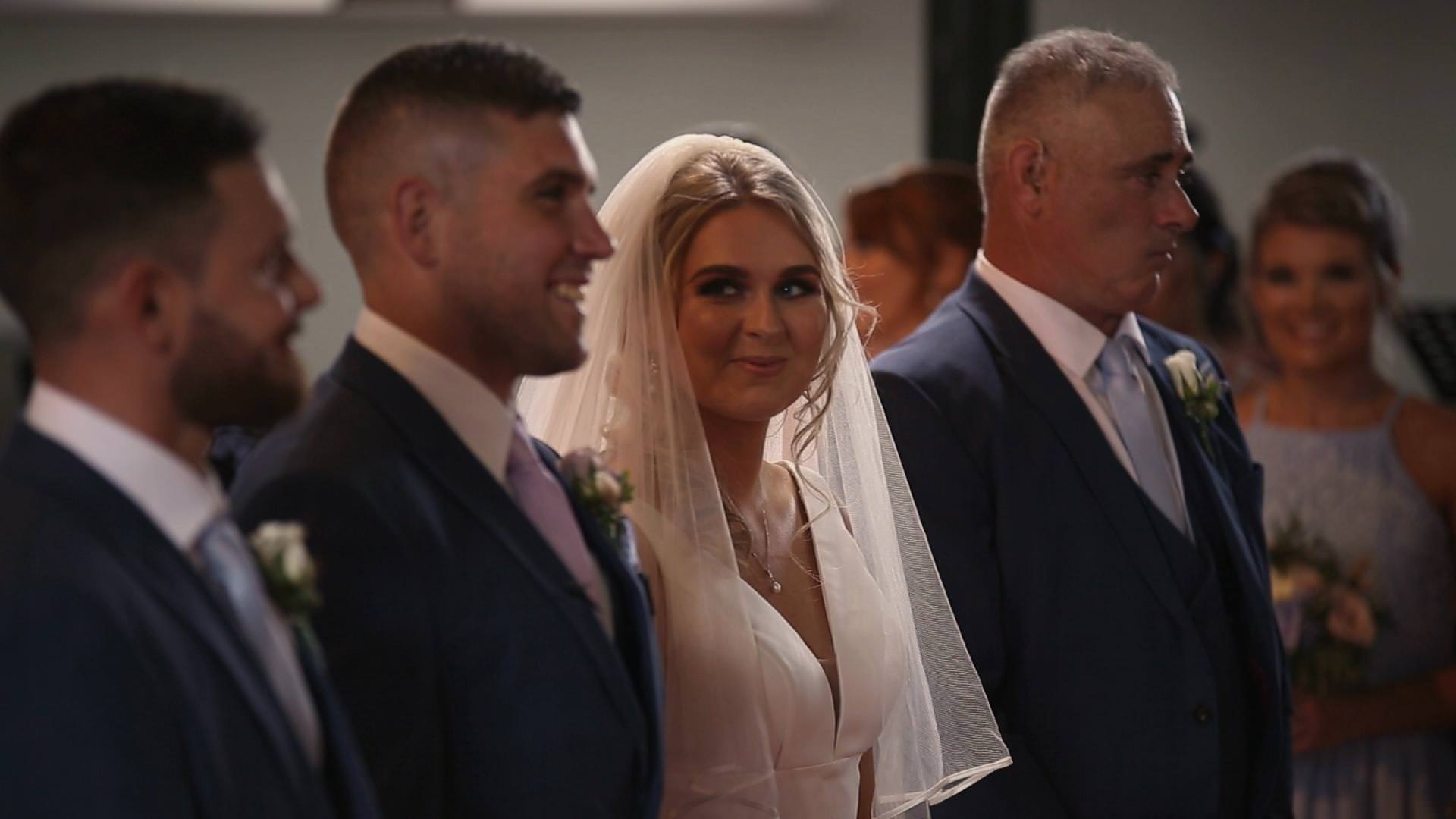 a wedding video still of a bride looking at her groom and smiling during the ceremony at St Johns church