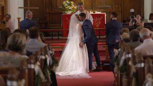 a bride and groom kiss at st johns church in burscough lancashire
