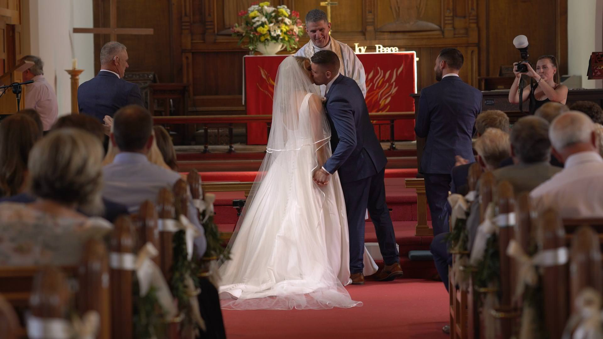 a bride and groom kiss at st johns church in burscough lancashire
