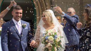 a wedding video still outside St Johns Church as they walk through confetti