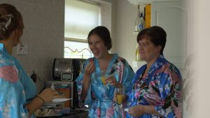 wedding video still of bridesmaids and mum laughing in matching silk kimono dressing gowns