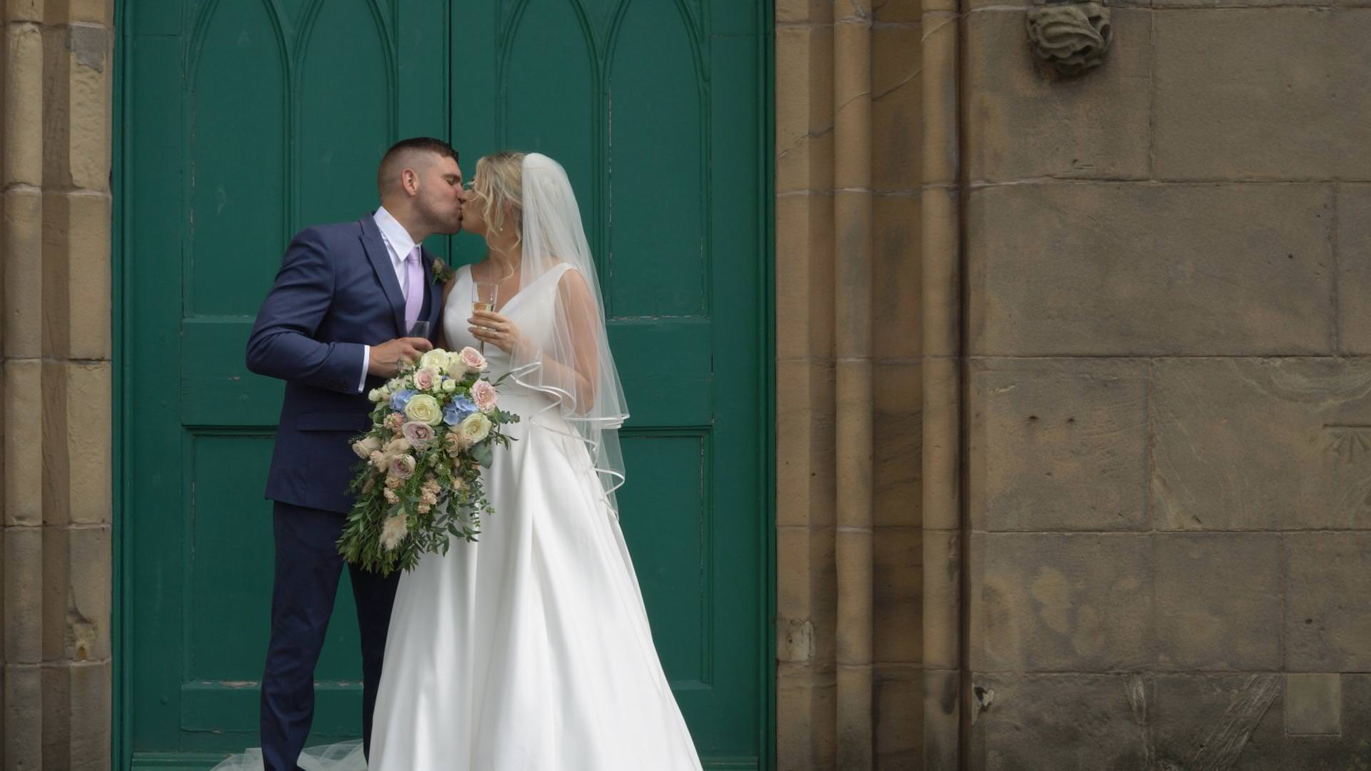 a full length wedding video still of a bride and groom kissing outside the green doors at St Johns Church