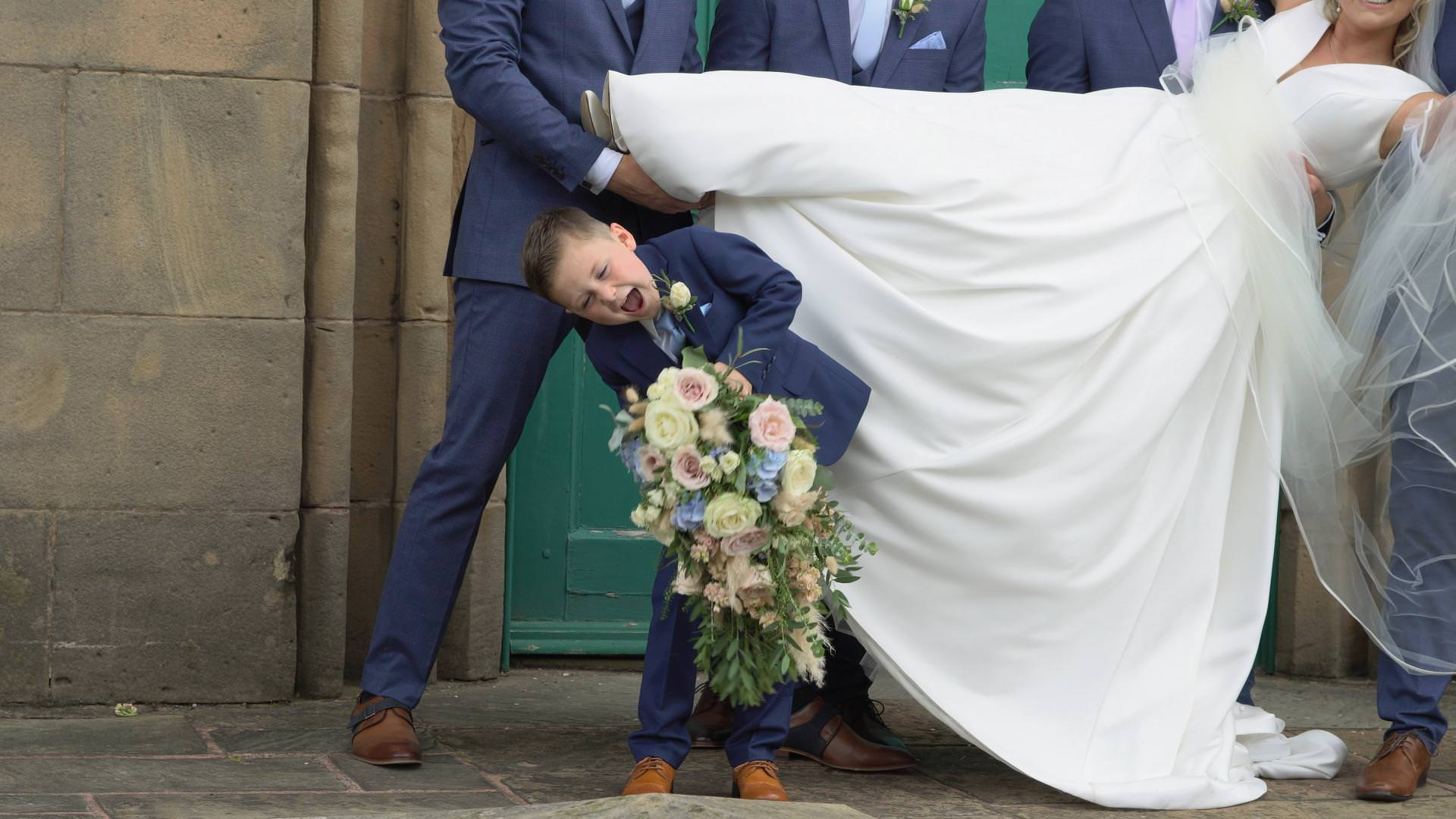 a page boy struggles to hold a heavy bridal bouquet in Lancashire