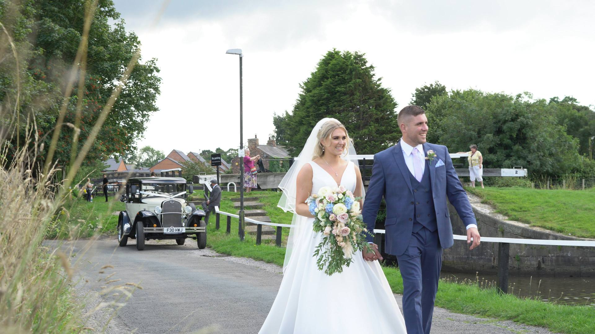 a bride and groom walk beside the leeds liverpool canal in Burscough during their wedding day