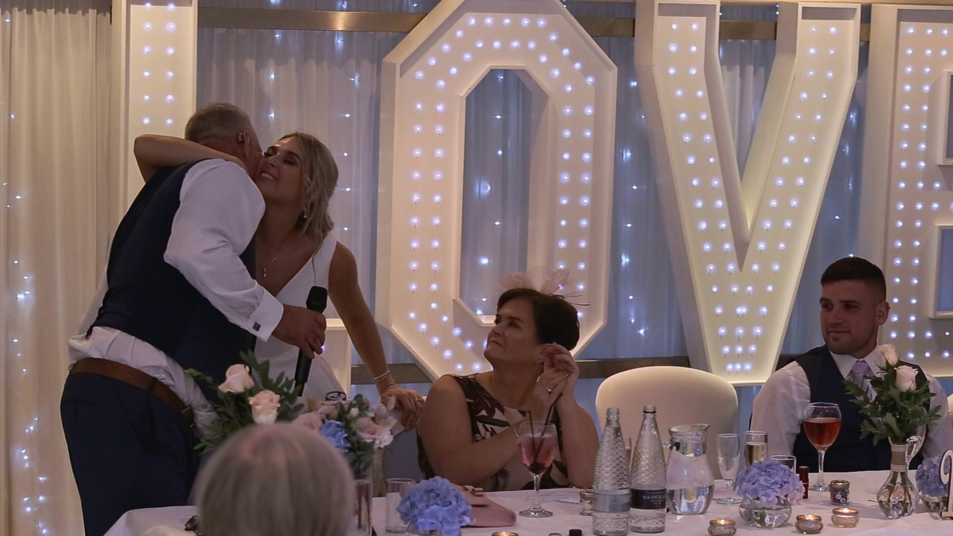 a video still of a bride kissing her dad after his emotional wedding speech at Briars Hall
