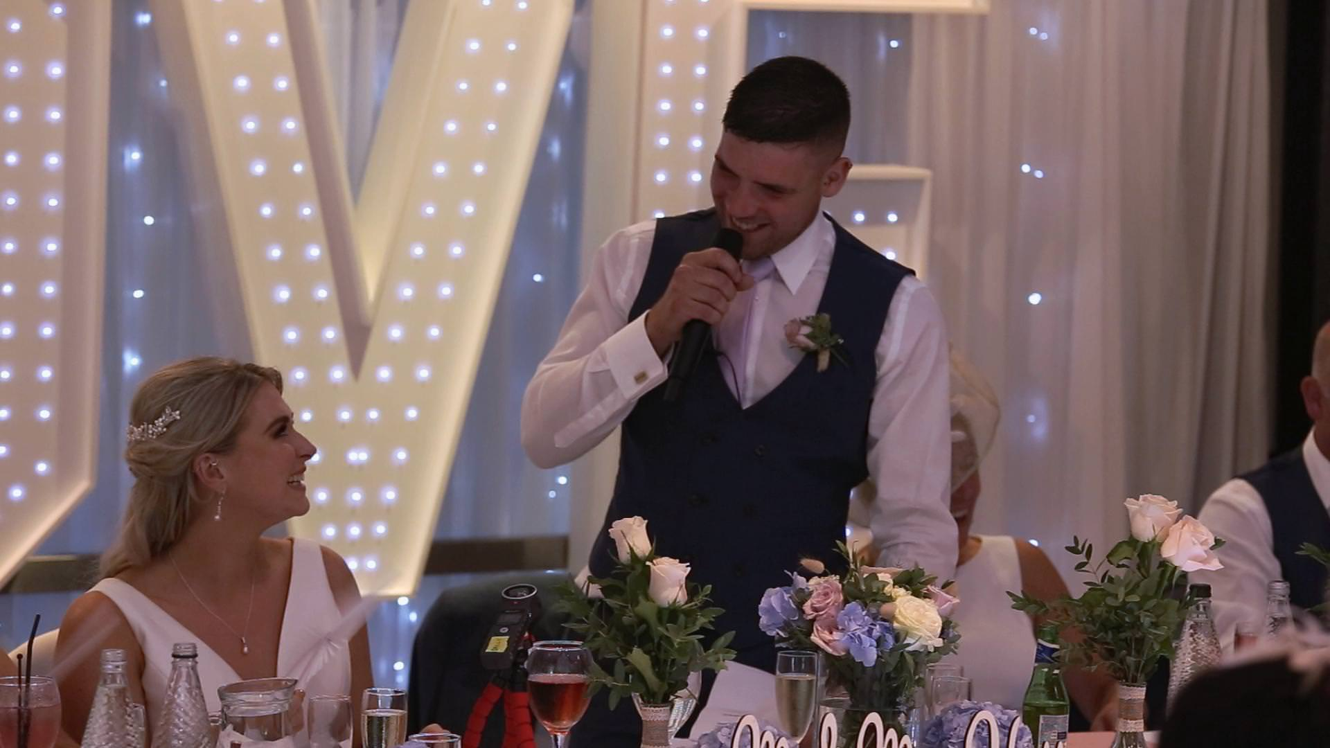 a groom laughs with his bride during his speech at Briars Hall