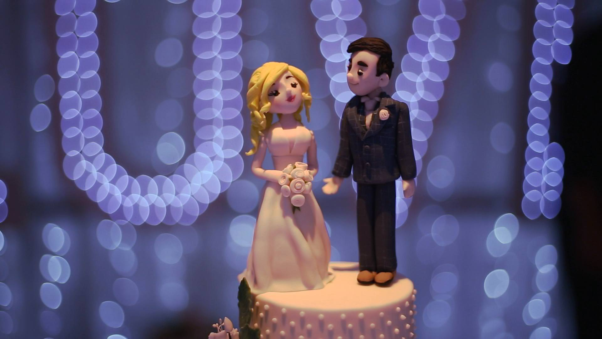 a close up video still of a fun wedding cake topper