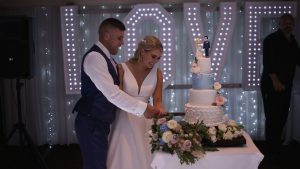 a bride and groom smile as they cut their 4 tier wedding cake at Briars Hall