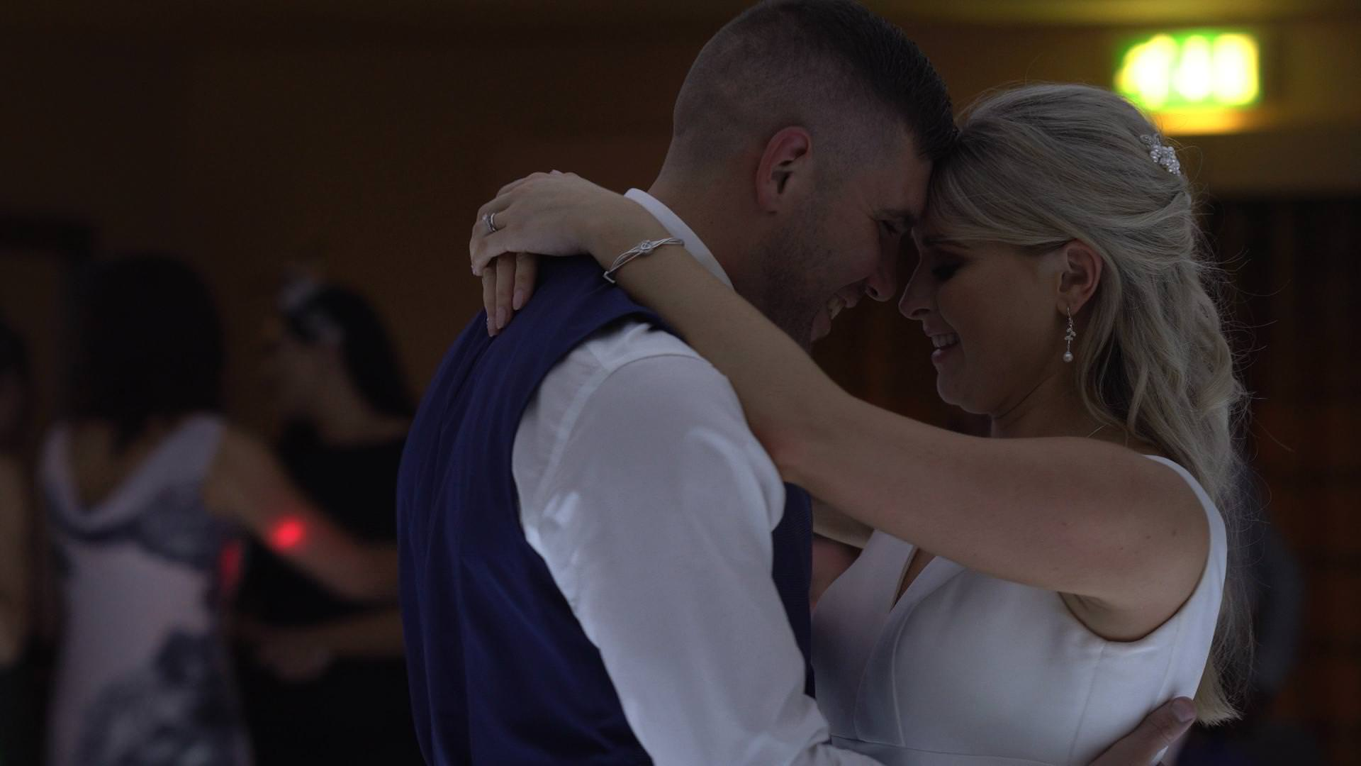 a wedding video still of a bride and groom touching heads during their first dance
