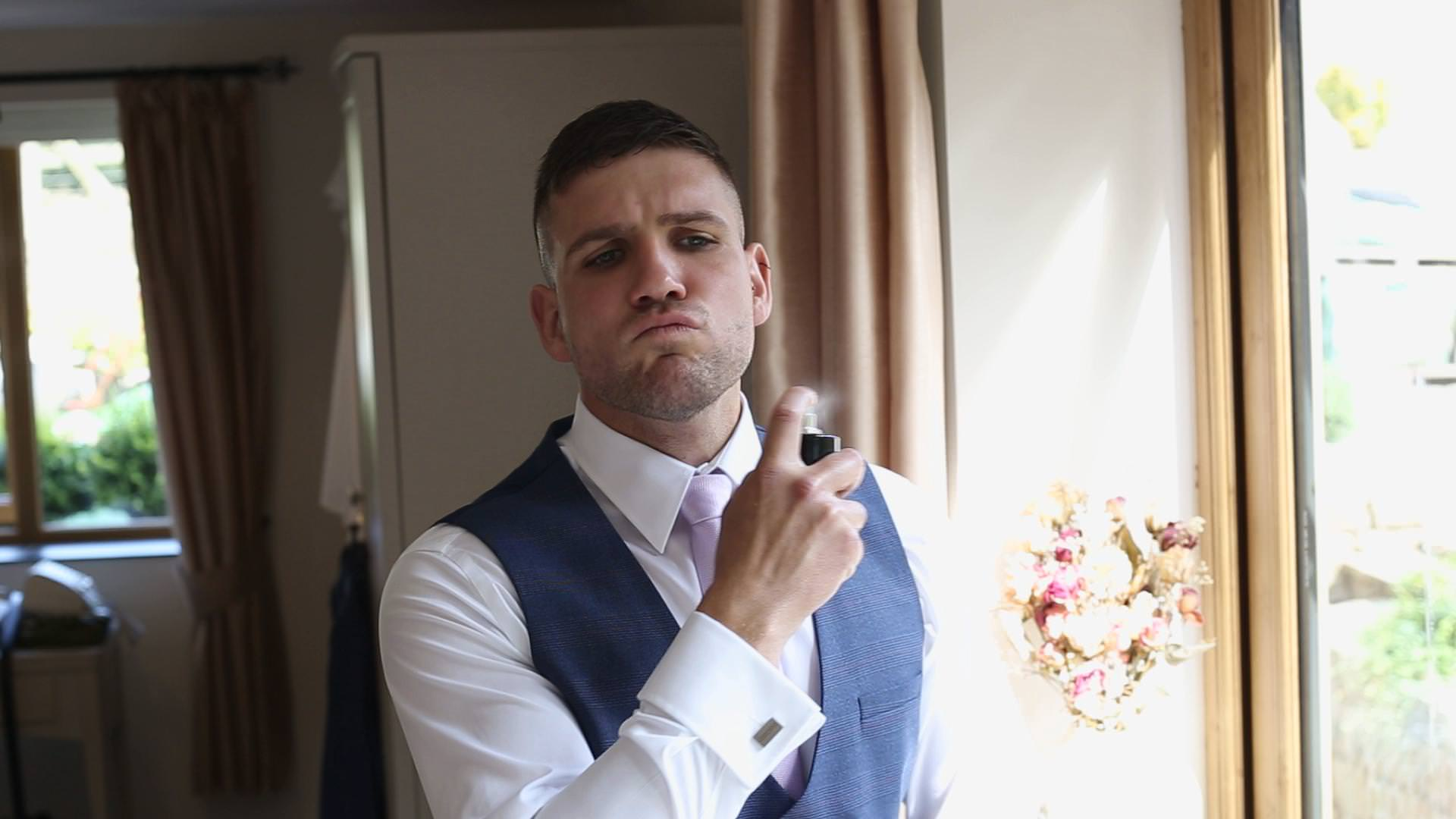 wedding video still of a groom spraying aftershave in Newburgh