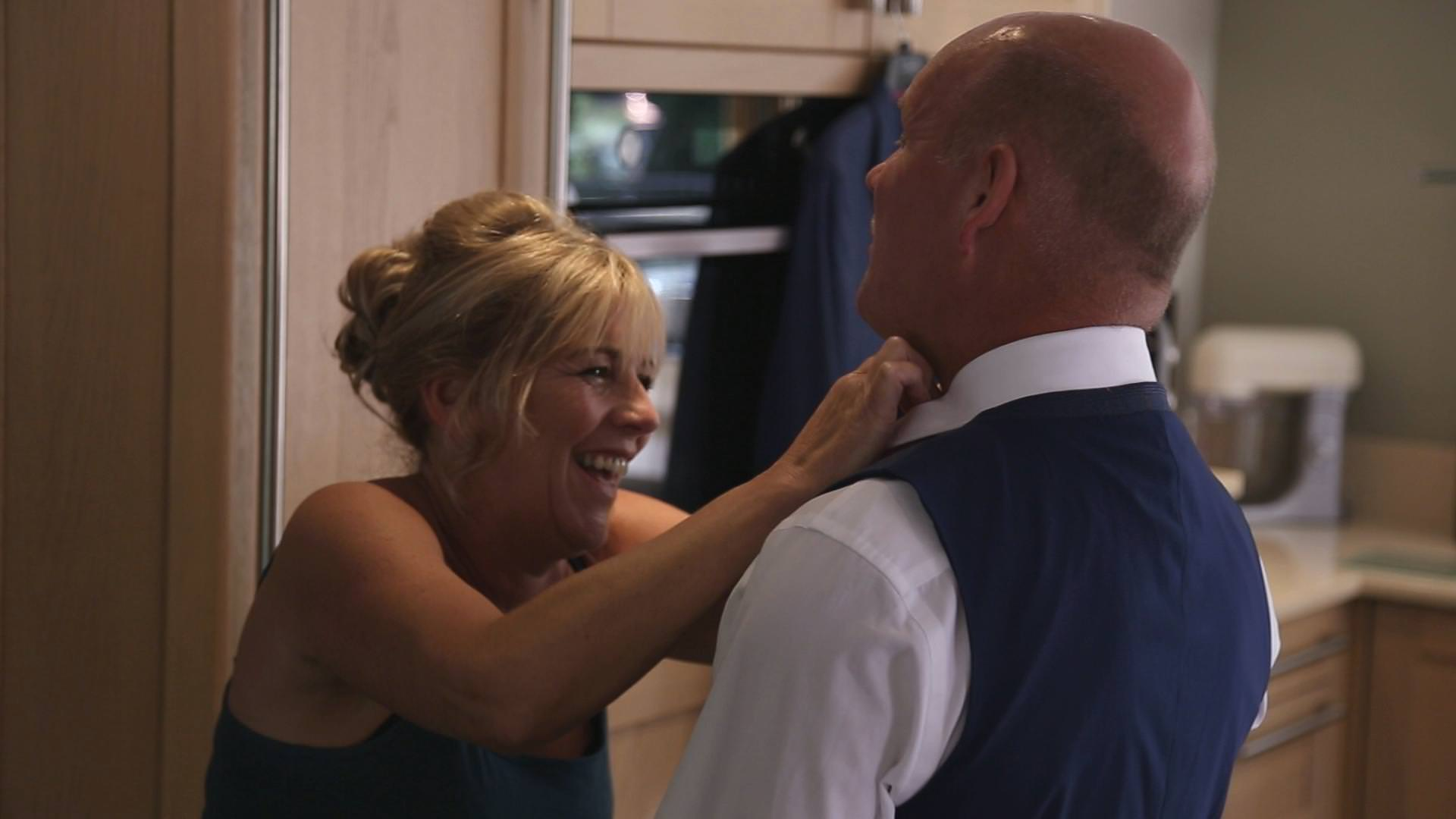 a wedding video still of a mother of the groom laughing at her husband