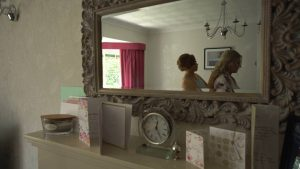 a video still of a mirror reflection of a bride getting ready at home in Newburgh
