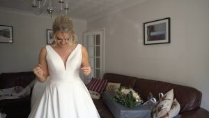 a bride stands in her classic silk wedding dress with pockets before her wedding in Burscough