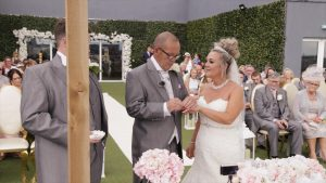 the groom puts a ring on the brides hand on the rooftop of the Shankly Hotel