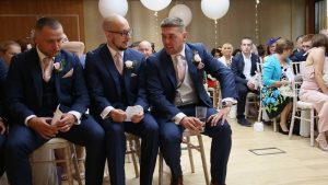a groom and best man sit front row at a wedding indoor ceremony at Moddershall Oaks