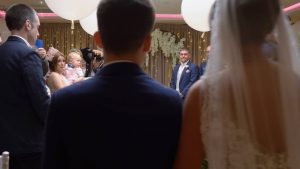Video still of a groom turns to see his bride walk down the aisle at Moddershall Oaks