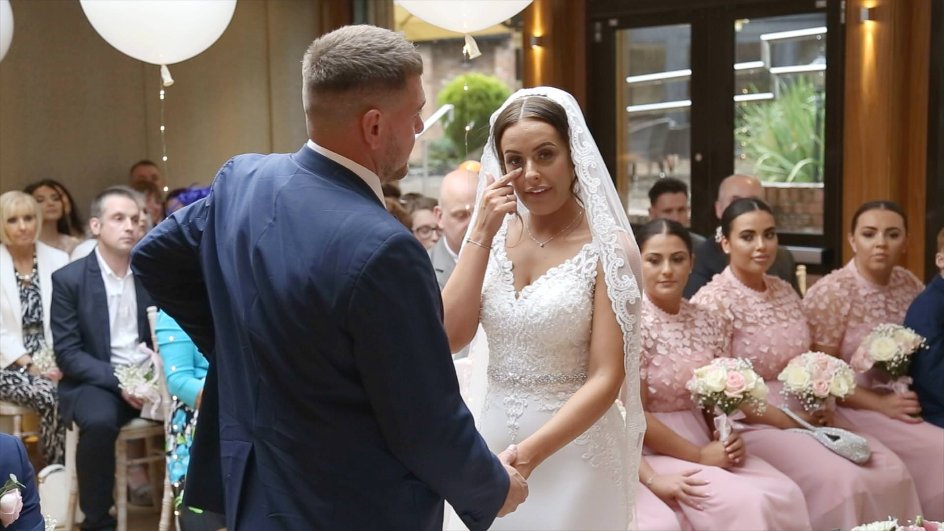 video still of a bride wiping away a tear during a Moddershall Oaks indoor ceremony