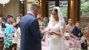 a groom puts on the brides wedding ring during their Moddershall Oaks ceremony