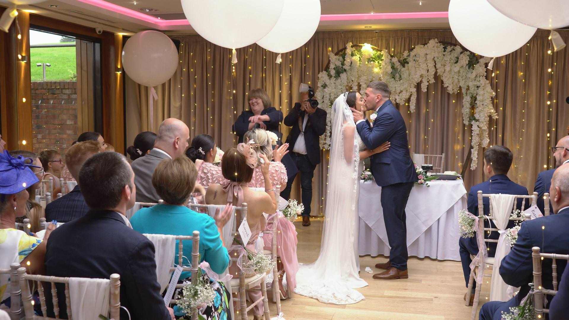 a wide of an indoor ceremony at Moddershall Oaks with big white balloons and hanging blossom