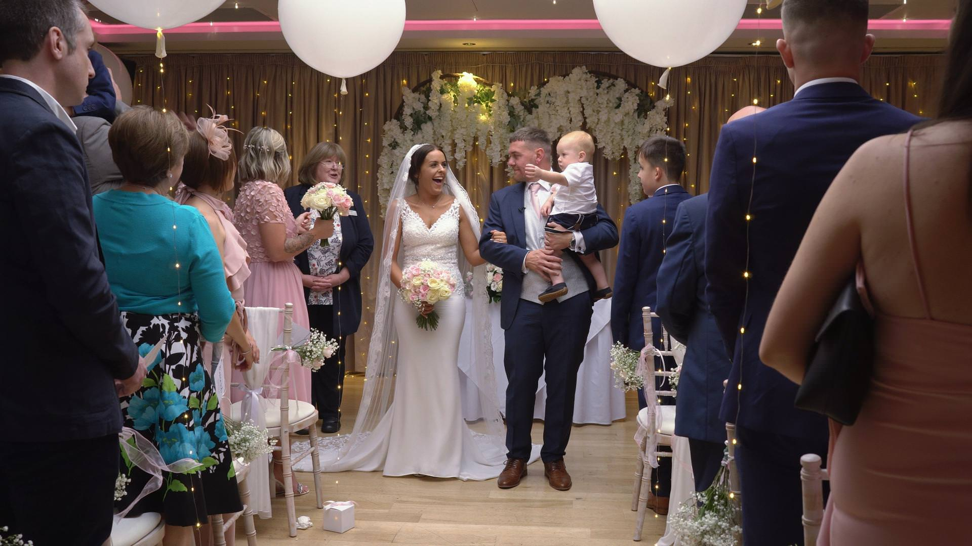 a bride and groom wait to walk down the aisle holding their baby boy in Staffordshire