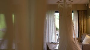 a wedding dress hangs from a four poster in a suite at Moddershall Oaks