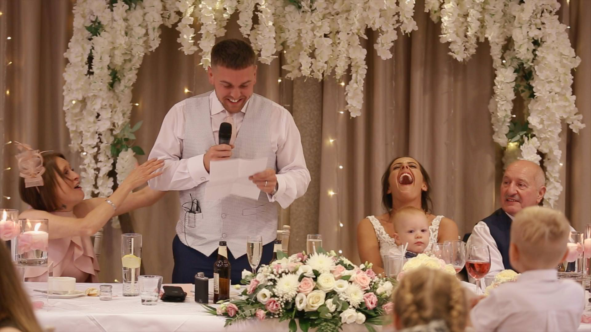 Bride laughs out loud during the grooms speech at Moddershall Oaks in Staffordshire