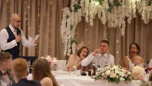 a video still of the top table during the wedding speeches at moddershall oaks