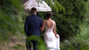 a bride and groom walk around the gardens at Moddershall Oaks holding a white umbrella