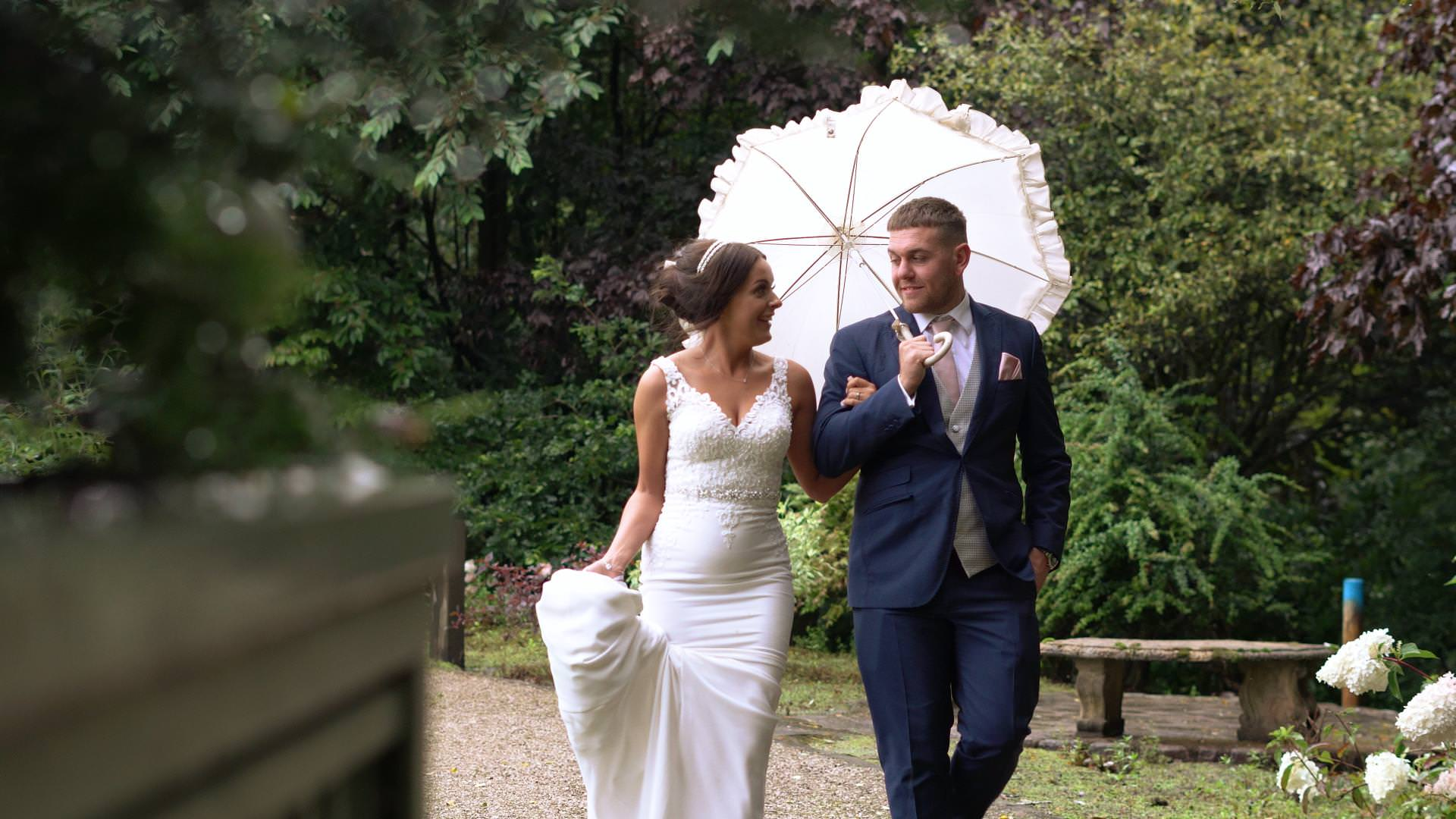wedding videographer still of a bride and groom walking in the rain at Moddershall Oaks in Staffordshire