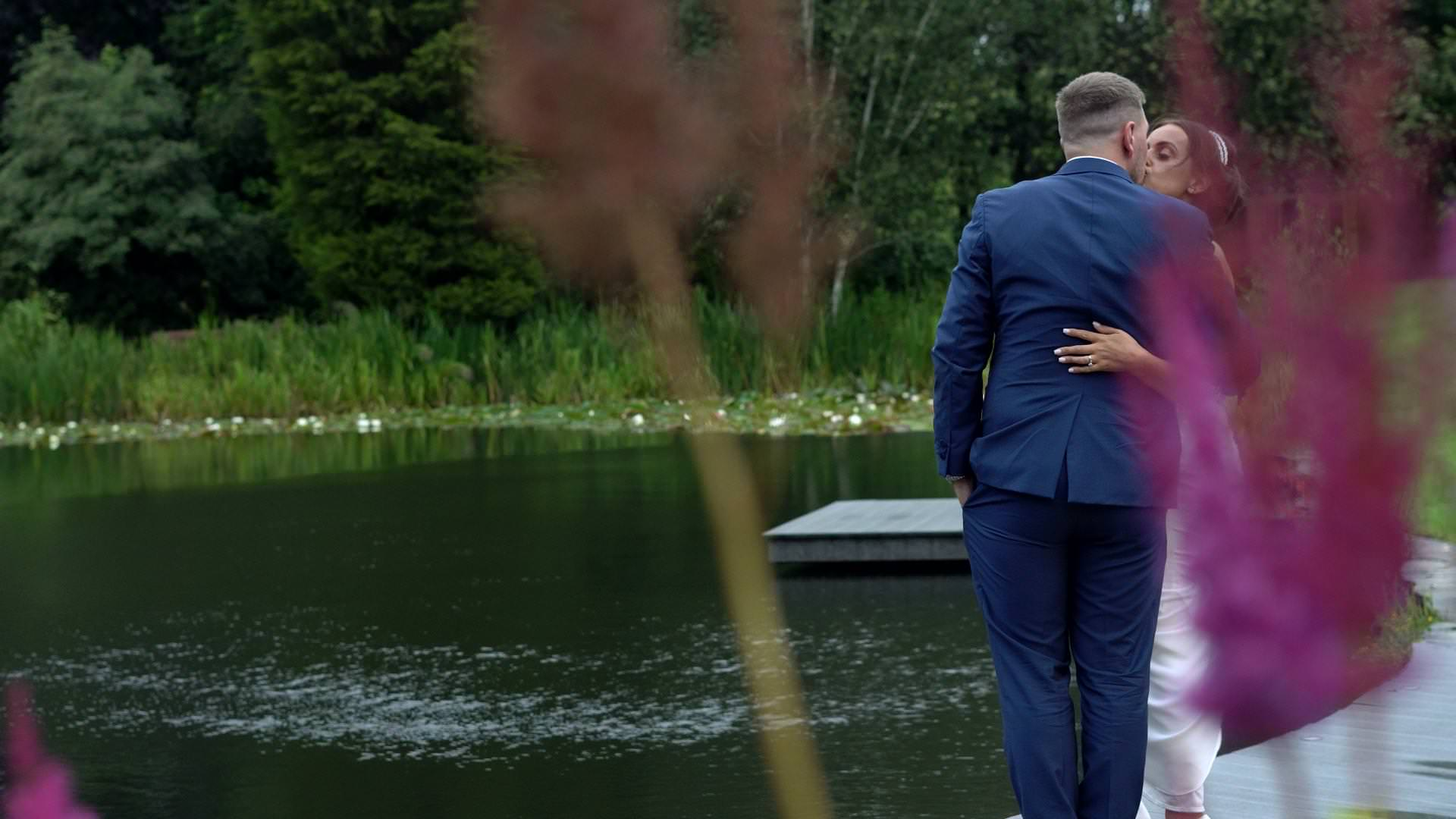 a bride and groom kiss on the lake at Moddershall Oaks