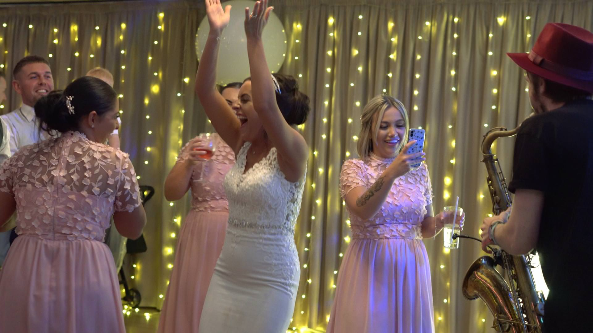 bride claps and dances with her bridesmaids at Moddershall Oaks