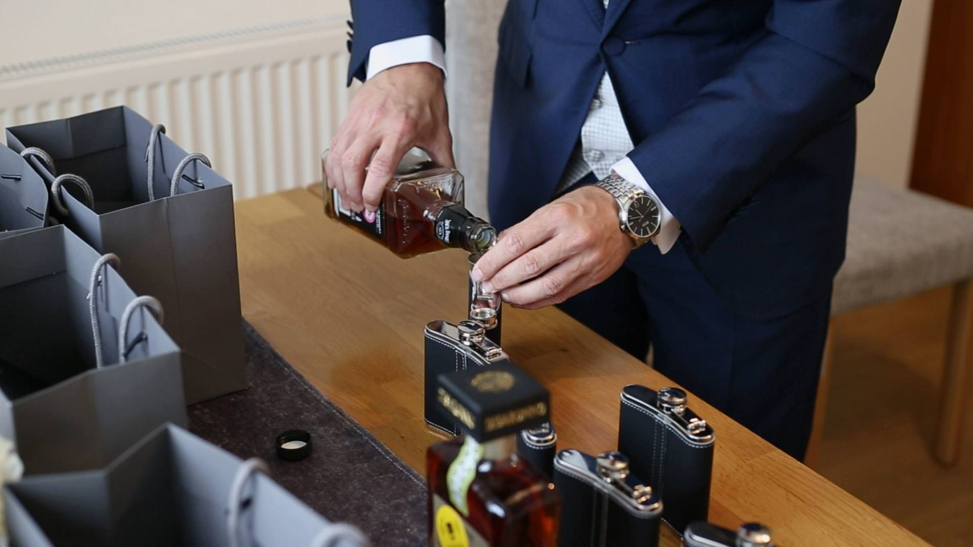 a close up video still of a groom pouring whisky in to wedding flask