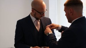 groom putting pink pocket square in to a best mans suit
