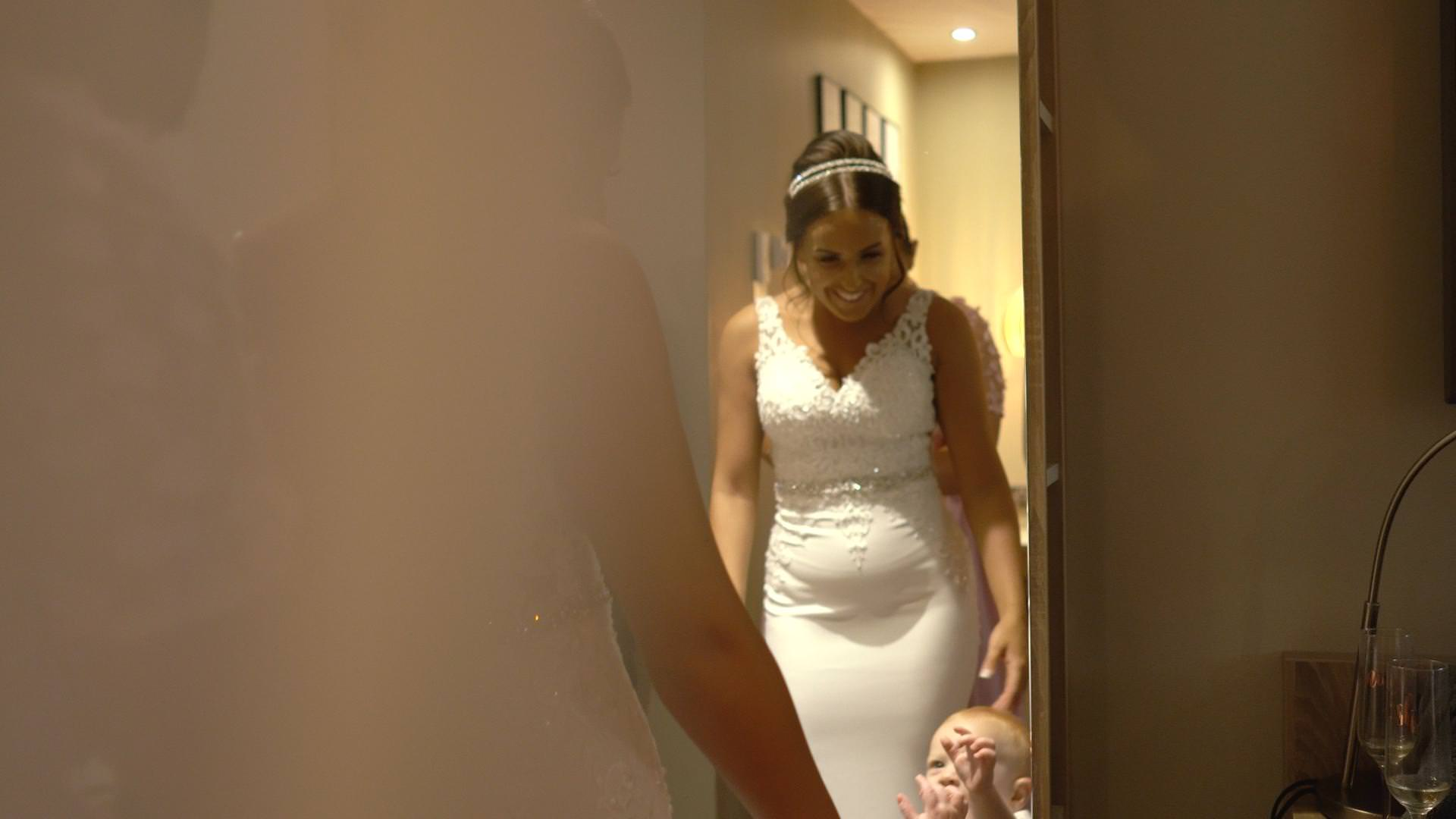 a bride smiles down at her son whilst getting in to her wedding dress at Moddershall Oaks