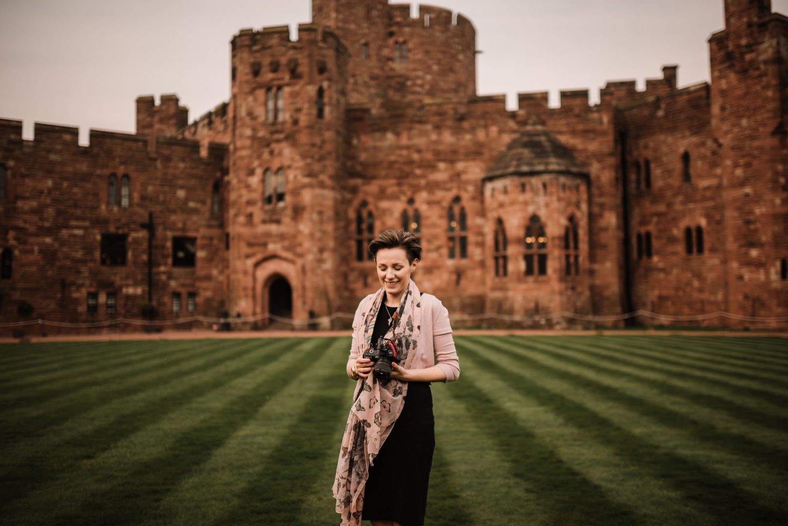 female wedding videographer holding a camera outside Peckforton Castle