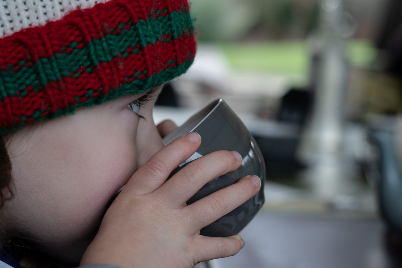 a photograph of a little girl in a wooly hat drinks hot chocolate