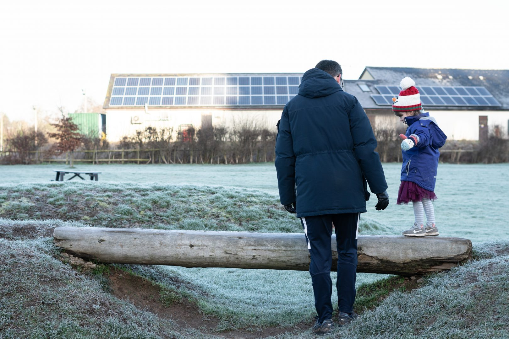 a photo of a dad and daughter play on a balance beam with thick winter frost