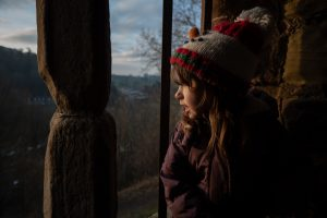 a girl in a winter snowman hat looks out a fairytale castle window for a family photoshoot