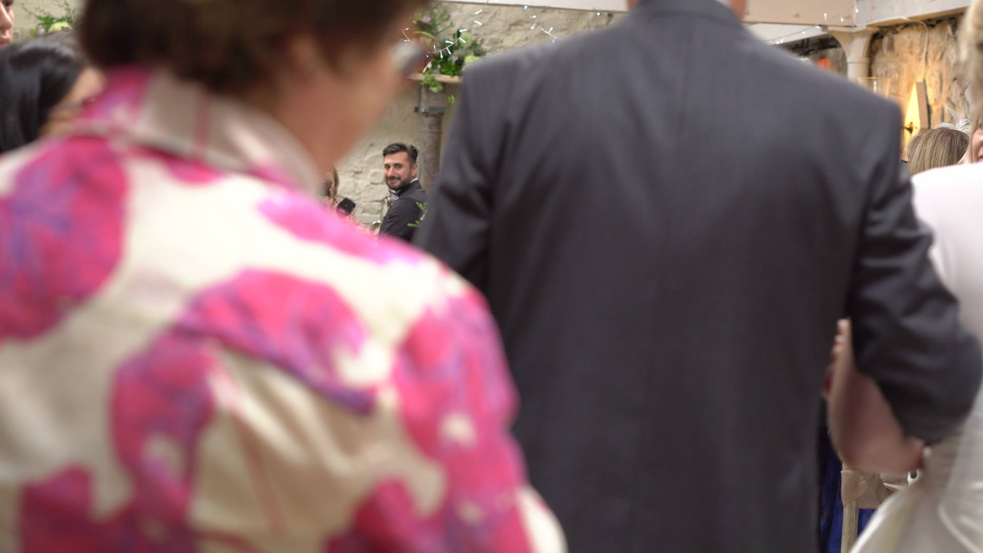 a video still of a groom turning to see his bride walk down the aisle