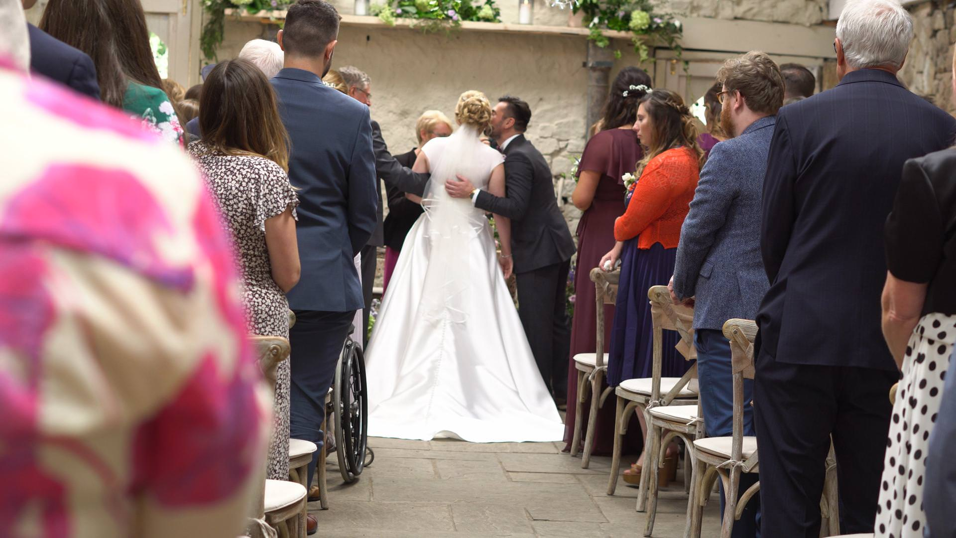 groom kisses the bride as they meet in the ceremony barn at Wyresdale