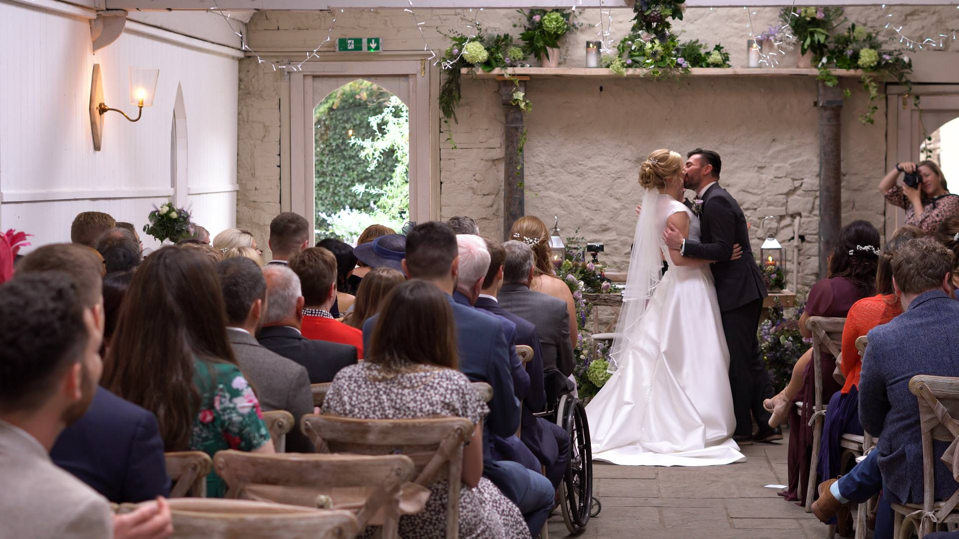 a video still of a bride and groom first kiss