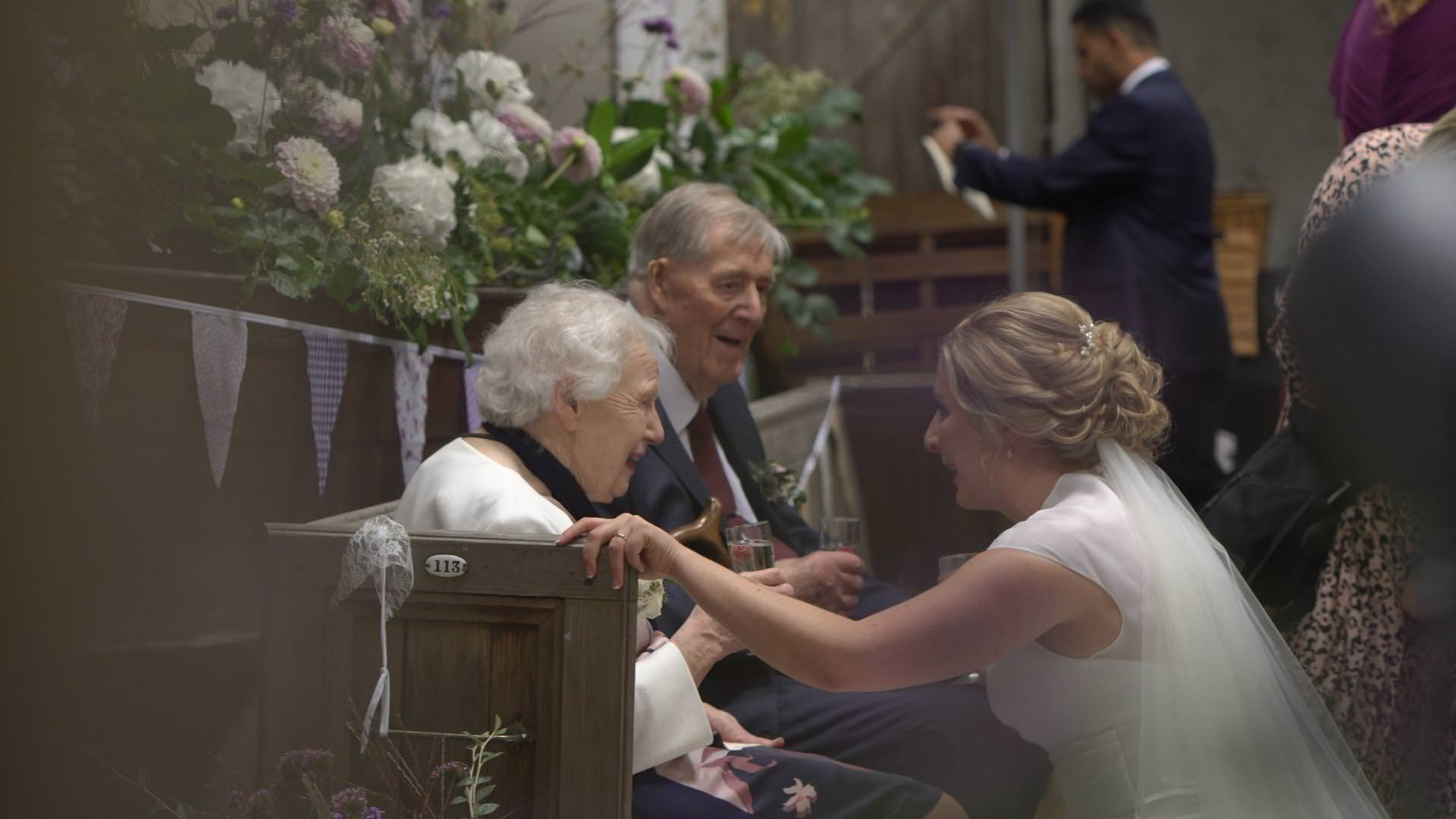 a bride crouches down to chat to her grandparents
