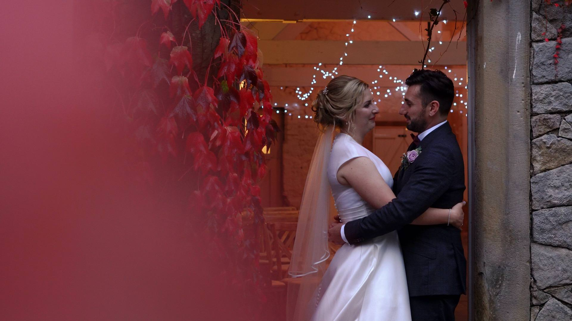 bride and groom cuddle by red leaves for wedding video