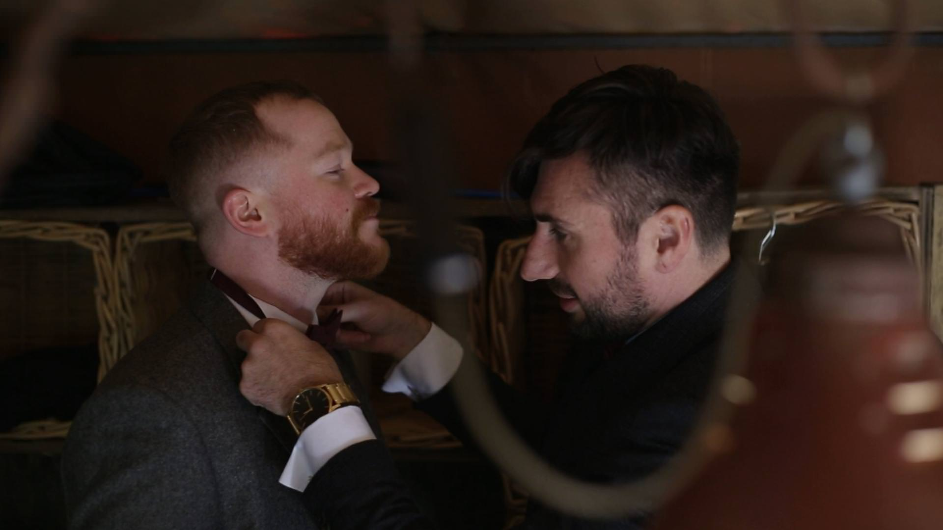 the groom sorts out a best mans bow tie