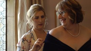 a bride helps her Mum in her dress