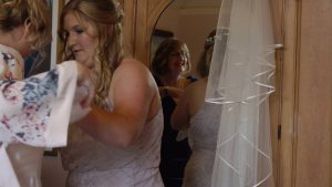 video of a mirror reflection of a bride getting in to her dress