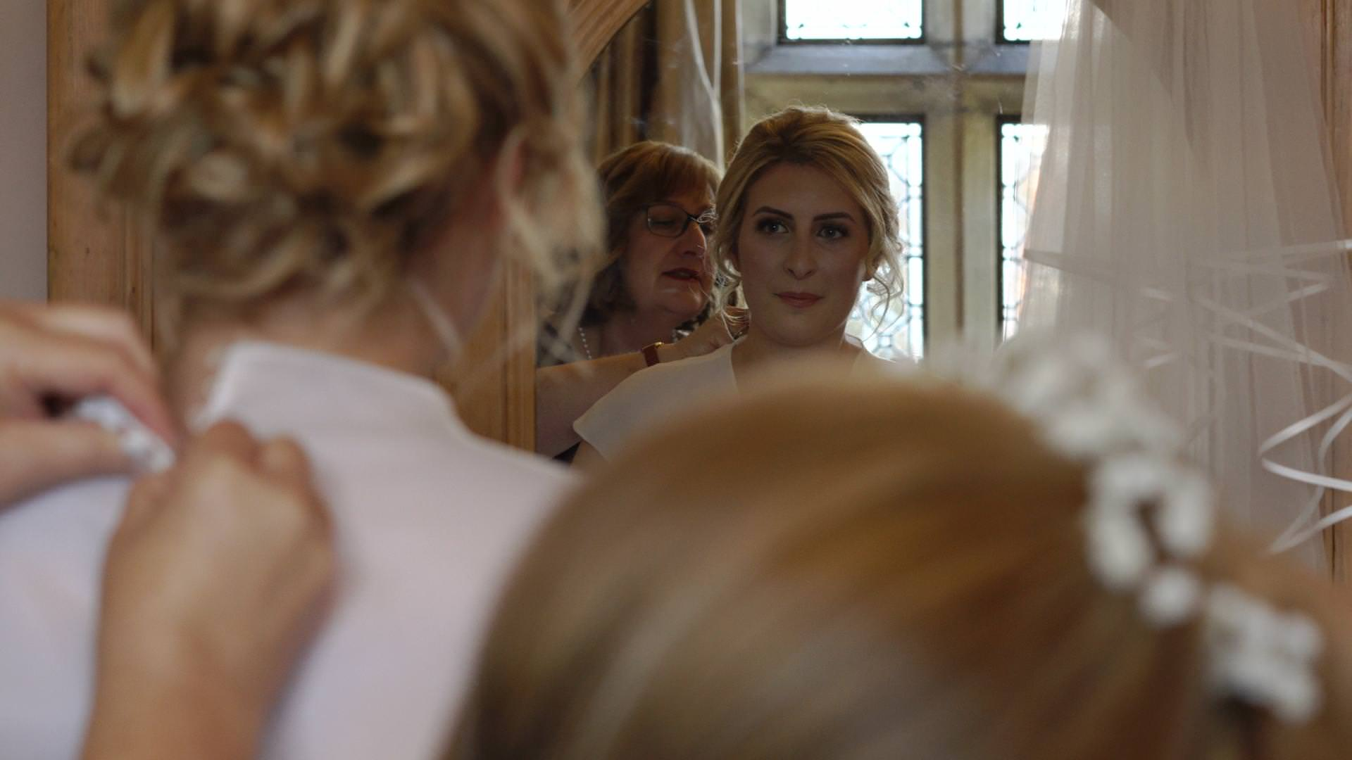 a bride looks at herself in a mirror in her dres at Wyresdale