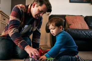 dad and son play with cars on their living room floor