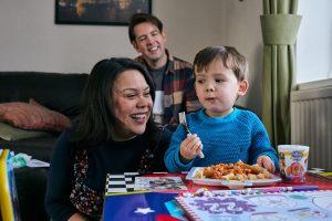 parents laugh as boy eats a whole sausage